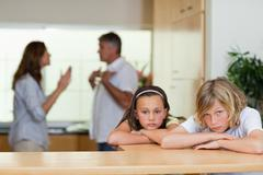 Sad looking siblings with arguing parents behind them - stock photo