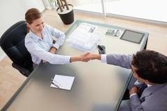 Stock Photo of Above view of consultant shaking hands with her client