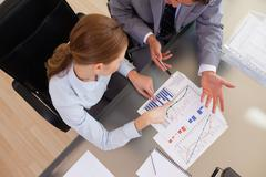 Above view of business people analyzing statistics - stock photo