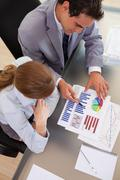 Above view of business people working with statistics - stock photo
