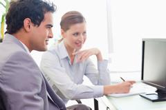 Mentor explains work to his new colleague - stock photo