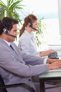 Call center agents working next to each other - stock photo
