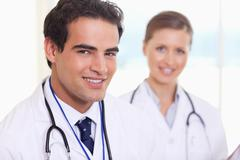 Smiling medical assistants standing next to each other - stock photo
