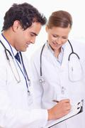 Assistant doctors taking notes - stock photo