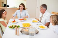 Stock Photo of Mother serving dinner to family