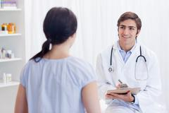 Smiling physician talking with patient - stock photo
