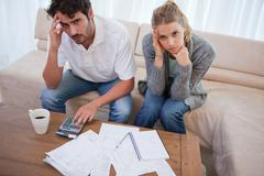 Worried couple doing their accounting - stock photo