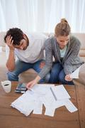 Portrait of a depressed couple doing their accounting Stock Photos