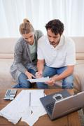 Portrait of a couple doing their accounting with a notebook - stock photo