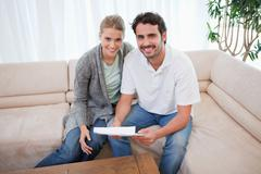 Smiling couple reading a letter - stock photo