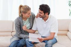 Happy couple reading a letter - stock photo