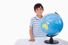 Stock Photo of Smiling boy posing with a globe