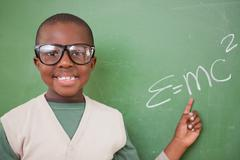 Schoolboy showing the the mass-energy equivalence formula - stock photo