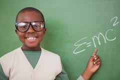 Smart schoolboy showing the the mass-energy equivalence formula - stock photo