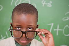 Schoolboy looking over his glasses - stock photo