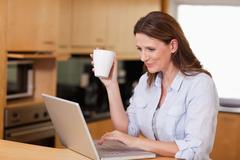 Stock Photo of Woman drinking tea while on laptop