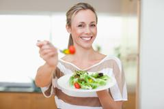 Woman offering healthy salad - stock photo