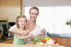 Smiling mother and daughter stirring salad - stock photo