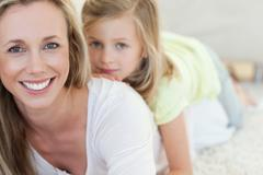 Mother and daughter lying on carpet - stock photo