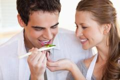 Man is tasting the meal his girlfriend is cooking - stock photo