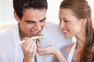 Stock Photo of Man is tasting the meal his girlfriend is cooking