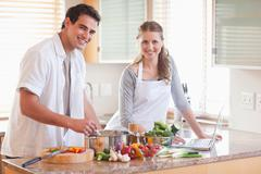 Couple using notebook to look up recipe - stock photo