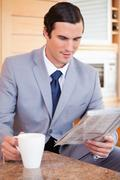 Stock Photo of Businessman in the kitchen reading news and having coffee