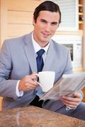 Businessman having coffee and reading news in the kitchen - stock photo