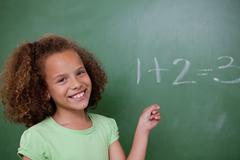 Cute schoolgirl pointing at an addition - stock photo