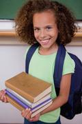 Portrait of a schoolgirl holding her books - stock photo