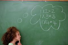 Schoolgirl thinking about algebra - stock photo