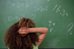Schoolgirl thinking about mathematics while scratching the back of her head - stock photo