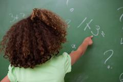 Schoolgirl pointing at an addition - stock photo