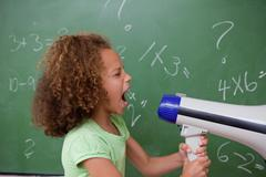 Side view of a schoolgirl screaming through a megaphone - stock photo
