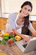 Portrait of a young woman looking for a recipe on the internet Stock Photos