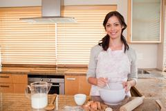 Stock Photo of Smiling woman baking