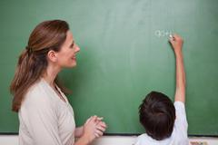 Happy schoolteacher helping a schoolboy doing an addition - stock photo