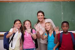 Stock Photo of Schoolteacher and her pupils waving at the camera