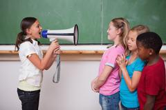 Schoolgirl yelling through a megaphone to her classmates - stock photo