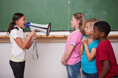Angry schoolgirl screaming through a megaphone to her classmates - stock photo