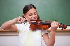 Schoolgirl playing the violin Stock Photos