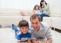 Dad and son lying on the carpet - stock photo