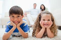 Stock Photo of Happy kids lying on the carpet with parents behind them