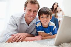 Stock Photo of Boy with his father using laptop on the carpet
