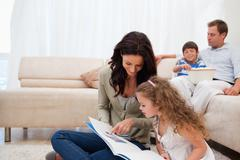 Stock Photo of Mother showing photo album to daughter