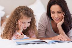 Little girl reading bedtime story with her mother - stock photo