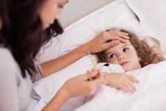 Mother taking care of her sick daughter - stock photo