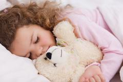 Stock Photo of Girl hugging her teddy while sleeping