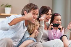 Stock Photo of Positive family playing video games together
