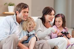 Competitive family playing video games together - stock photo